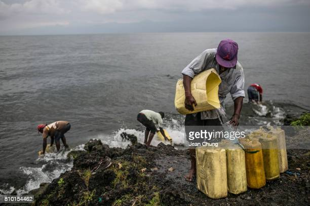 Congolese water seller at right pours lake water onto the containers on the rocky shore of the Kivu Lake on June 9 2014 in Goma Democratic Republic...