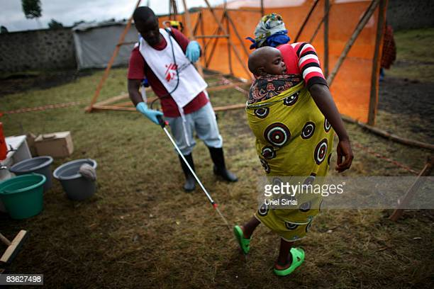 A Congolese woman gets her feet disinfected to prevent the spread of cholera outside an Medecins Sans Frontieres tent clinic at the Kibati refugee...