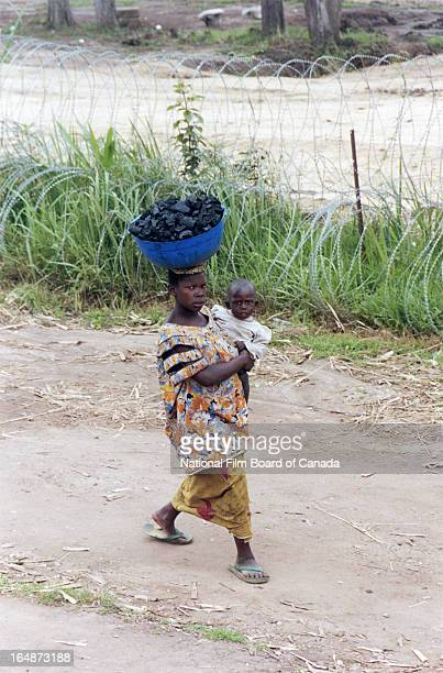 A Congolese woman holding her child in her arms walks past a barbed wire fence that surrounds a camp for internally displaced people on the outskirts...