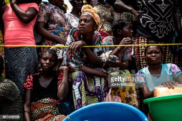 A Congolese woman looks on while people wait for their ration of food to be handed out at a food distribution on October 25 2017 in Kasala in the...