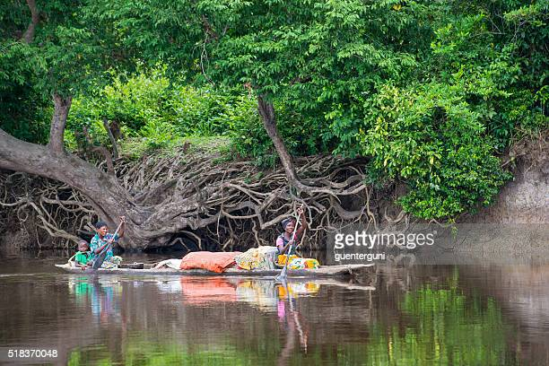 Congolese women are paddling in a pirogue on Congo River