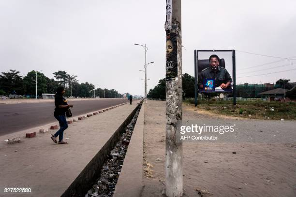 A Congolese women crosses an empty boulevard in Kinshasa with a placard of President of the Democratic Republic of Congo Joseph Kabila as the...