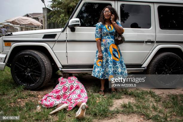 Congolese women take cover behind a car after police fired warning shots to disperse a crowd at the end of a Catholic service that commemorates the...