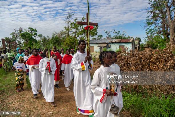 TOPSHOT A congregant holds a holy cross walking past rubbles during a march to commemorate Palm Sunday on April 14 2019 at Lady of Grace Parish...