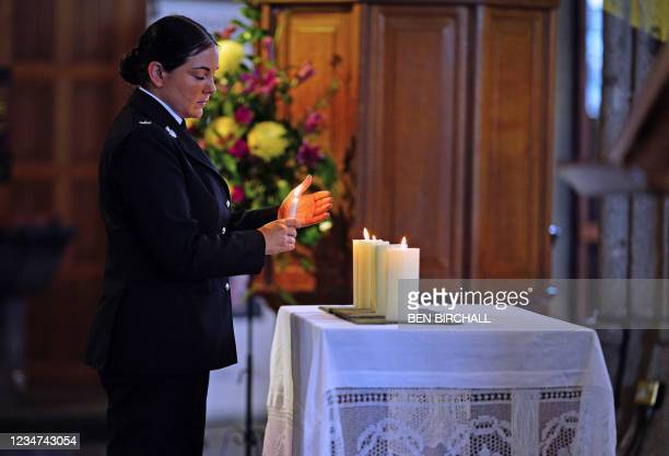 Congregant lights a candle during a civic service at Minister Church Of St Andrew in the Keyham area of Plymouth, southwest England, on August 18,...