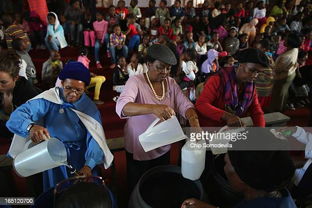Congregants fill bottles with holy water after Easter services at Regina Mundi Catholic Church in the Soweto area March 31 2013 in Johannesburg South...