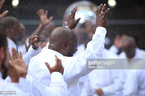 Congregants with arms raised during the spray of water The United House of Prayer for All People staged its annual street baptism in Harlem