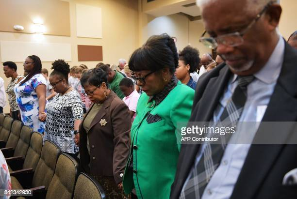 Congregation members join hands as they pray during Sunday Service at the Fifth Ward Church of Christ in Houston on September 3 2017 / AFP PHOTO /...