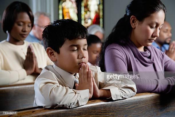 Congregation praying in church, eyes closed