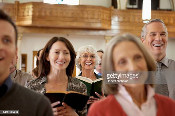 congregation singing together in church - kirche stock-fotos und bilder