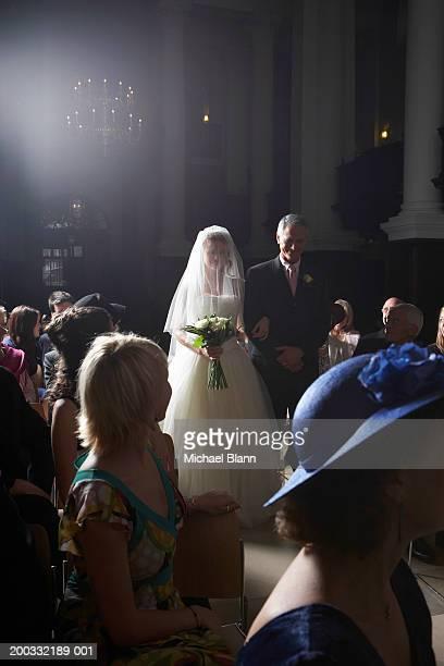 Congregation watching father walking bride down church aisle, smiling