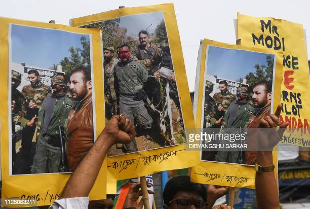 Congress activists shout slogans against Pakistan as they hold posters and pictures of captive Indian Air Force pilot Abhinandan Varthaman demanding...
