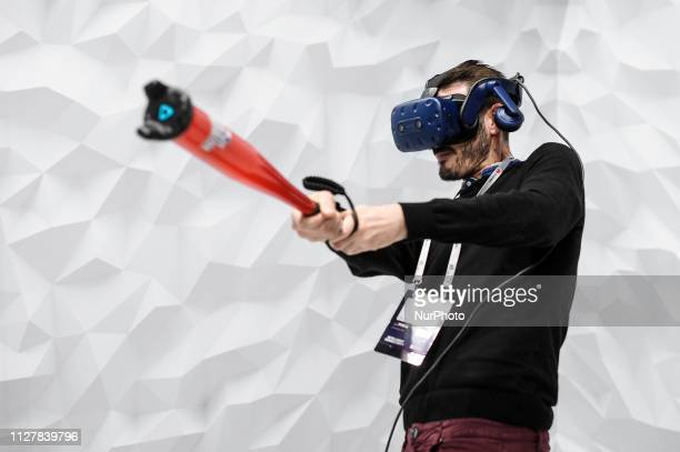 A congress assistant playing baseball with the HTC Vive Pro during the Mobile World Congress on February 27 2019 in Barcelona Spain