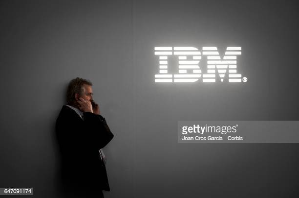 A congress attendee speaks on his mobile phone in front of IBM logo during the Mobile World Congress on March 1 2017 in Barcelona Spain