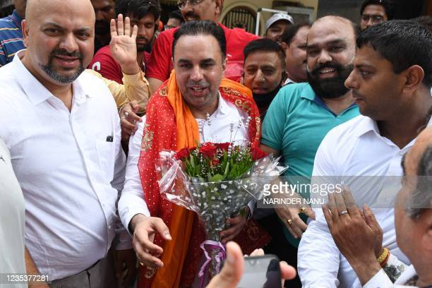 Congress leader Vikas Soni holds flowers presented by Congress workers as they celebrate after newly appointed Punjab Chief Minister Charanjit Singh...