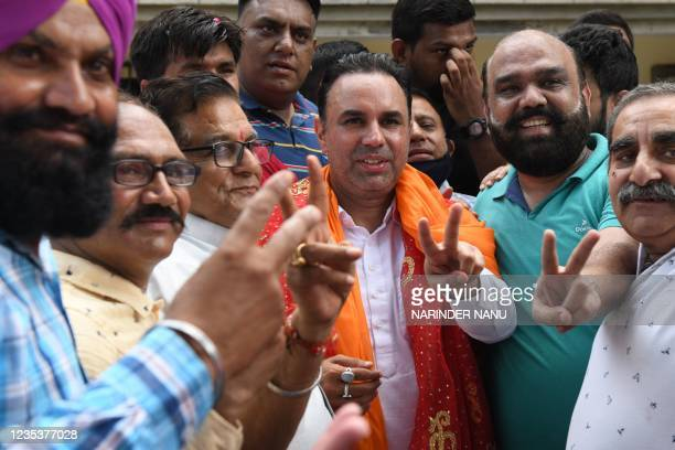Congress leaders Vikas Soni Jugal Kishore Sharma and Congress workers gesture as they celebrate after newly appointed Punjab Chief Minister Charanjit...