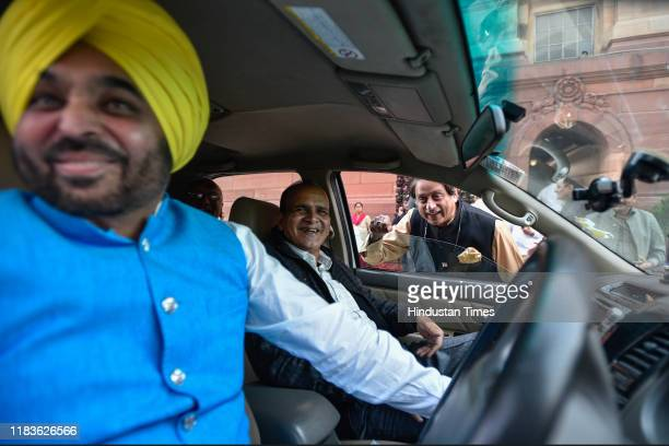 Congress Member of Parliament Shashi Tharoor shares a light moment with Aam Aadmi Party MP Bhagwant Mann during the winter session of Parliament on...