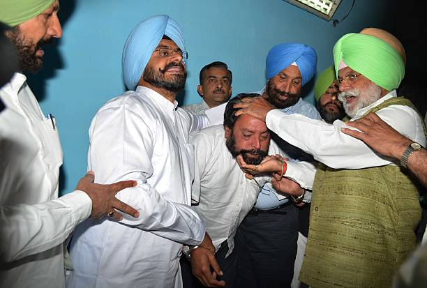 Congress MLAs Gurjit Rana and Kuljit Nagra trying to show the face of one of the constables who were roaming outside the CLP office at Punjab Vidhan..