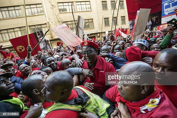 Congress of South African Trade Unions Secretary General Zwelinzima Vavi is surrounded by supporters as he arrives to address striking members South...