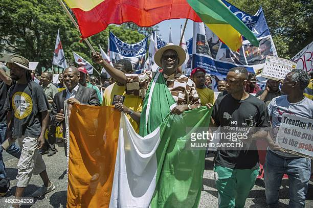 Congress of South African Trade Unions Secretary General Zwelinzima Vavi holds an Ivorian national flag as rights activists and protesters march...