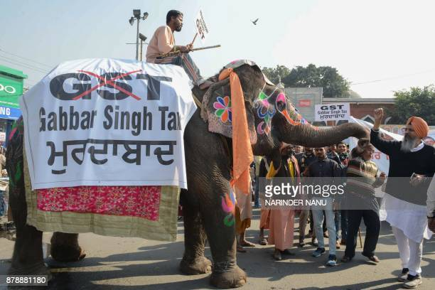 Congress Party activists gather around an elephant as they protest against the central Indian government and the Goods and Services Tax in Amritsar...