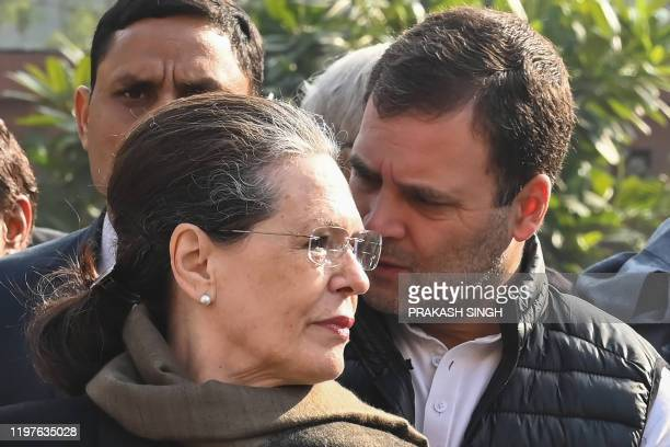 Congress Party president Sonia Gandhi listens to his son and former party president Rahul Gandhi as they join with other leaders to protest against...