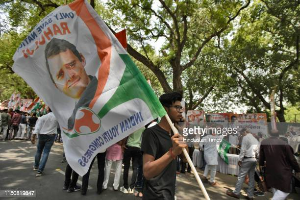 Congress party supporter holds a flag with the portrait of Indian National Congress President Rahul Gandhi during his 49th birthday celebrations,...