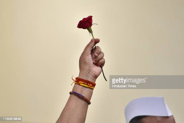 Congress party supporter holds a rose as she waits for Indian National Congress President Rahul Gandhi's arrival during his 49th birthday...