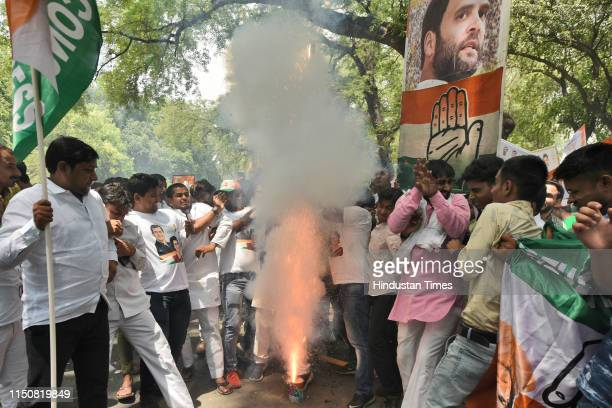 Congress party supporters burst crackers as they celebrate Indian National Congress President Rahul Gandhi's 49th birthday, outside party...