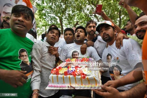 Congress party supporters hold a cake as as they celebrate Indian National Congress President Rahul Gandhi's 49th birthday, outside party...