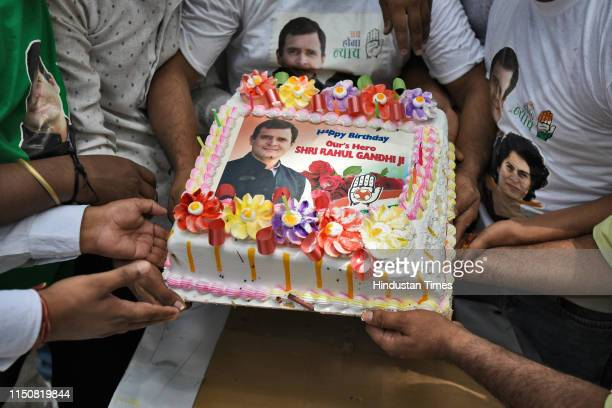 Congress party supporters hold a cake as they celebrate Indian National Congress President Rahul Gandhi's 49th birthday, outside party headquarters,...