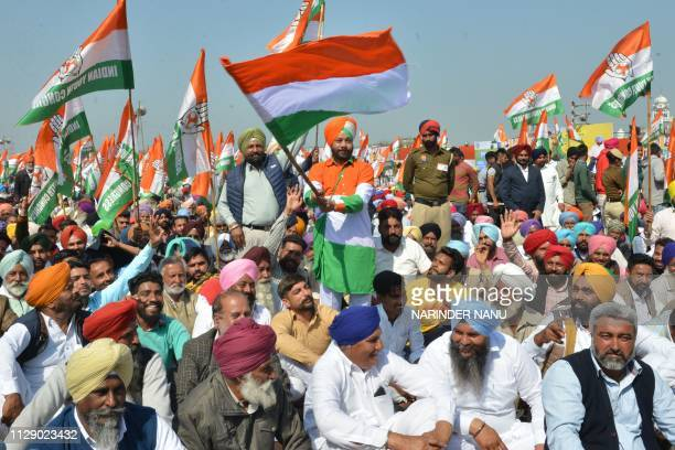 Congress party supporters hold party flags during the launch of the party's campaign in Punjab ahead of the upcoming Lok Sabha elections at a...
