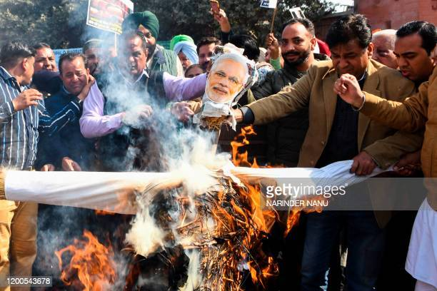 Congress Party workers shout slogans as they burn an effigy of Indian Prime Minister Narendra Modi during a protest against the price hike ofthe...