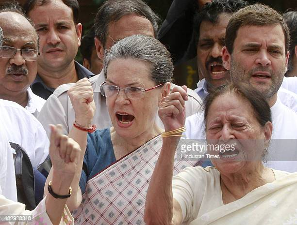 Congress President Sonia Gandhi and Congress Vice President Rahul Gandhi shouting slogans with the party members in front of the Gandhi statue during...