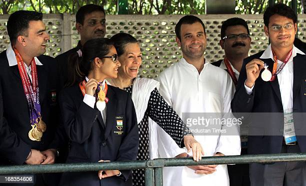 Congress President Sonia Gandhi and her son Rahul Gandhi pose for a photo with Indian shooters Gagan Narang Heena Sidhu Deepak and others who won...