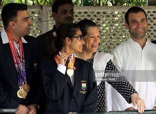 Congress President Sonia Gandhi and her son Rahul Gandhi pose for a photo with Indian shooters Gagan Narang Heena Sidhu who won medals in the just...