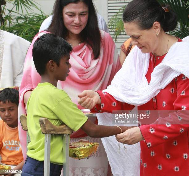 Congress President Sonia Gandhi tying a rakhi to a physicallychallenged boy on the occasion of 'Raksha Bandhan' at her residence on August 16 2008 in...
