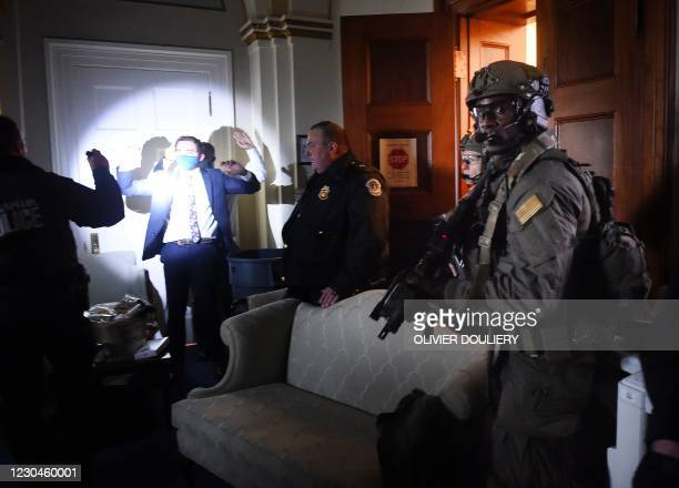 Congress staffers hold up their hands while Capitol Police Swat teams check everyone in the room as they secure the floor of Trump suporters in...