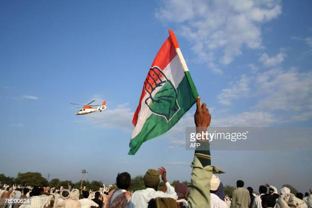 A Congress supporter waves a party flag as the helicopter carrying Congress Party President Sonia Gandhi leaves after a public meeting in Jasdan town...