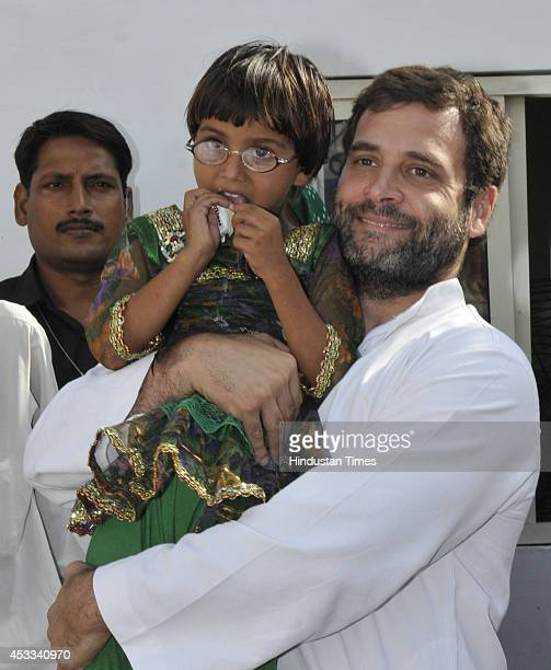Congress vice president Rahul Gandhi holds a child in his lap during inauguration of Indira Gandhi Eye Hospital at Raipur Sohna on August 8 2014 in...