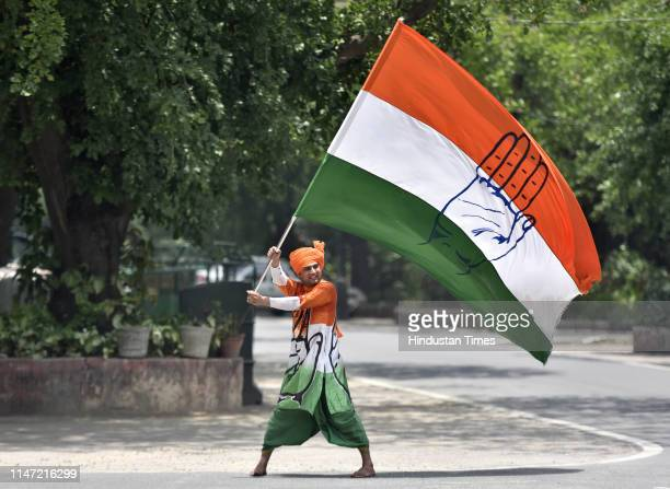 Congress worker waves party flag during a protest outside Rahul Gandhis residence urging him to continue as Congress President at Tughlaq Lane on...