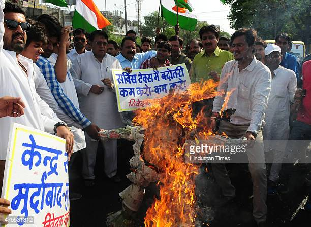 Congress workers burning an effigy of BJP government during a demonstration to protest against hike in service tax on June 1, 2015 in Bhopal, India....