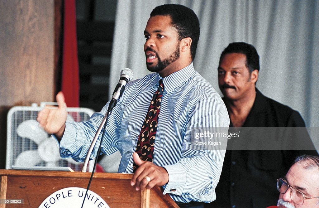 Congressional candidate Jesse Jackson Jr. speaking at podium while his civil rights activist father, Rev. Jesse Jackson, stands behind him.