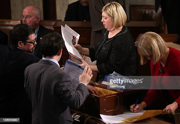 Congressional clerks open certificate envelopes from different states during a joint session of the 113th Congress to count the Electoral College...