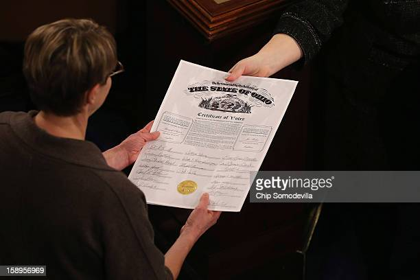 Congressional clerks pass the Electoral College certificate from the state of Ohio while unsealing and organizing all the votes from the 50 states in...