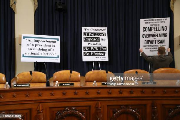 A congressional staffer puts up signs prior to testimony by constitutional scholars before the House Judiciary Committee in the Longworth House...