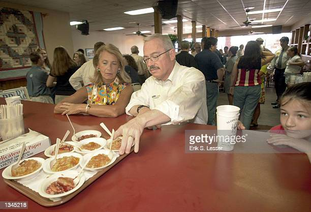 Congressman Bob Barr reaches for some peach cobbler at Slope's Barbeque August 4 2002 in Woodstock Georgia Barr is running for reelection against...