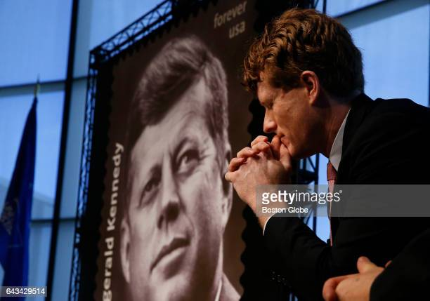 Congressman Joe Kennedy III listens to a speaker beside a Forever stamp in commemoration of the centennial of President John F Kennedy's birth at the...