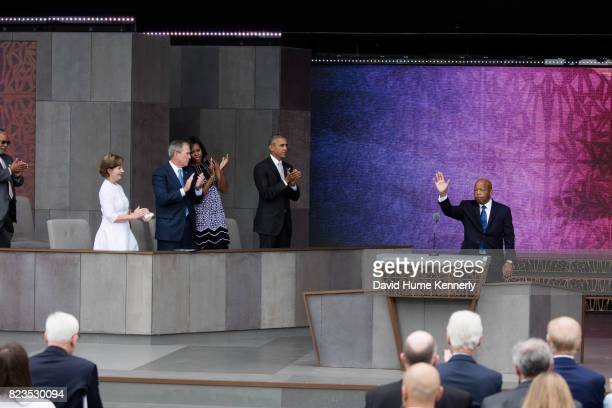 Congressman John Lewis waves as he receives a standing ovation at the opening of the National Museum of African American History and Culture...