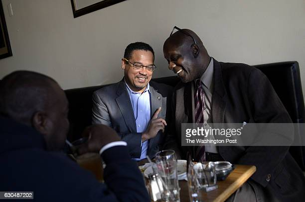 Congressman Keith Ellison center talks with college friend Terry Price right and Gary Jones left while at 1917 American Bistro in Detroit United...